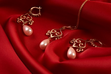 Beautiful precious womens jewelry, close-up. Pearl Golden Necklace and Earrings on red silk background with copy space