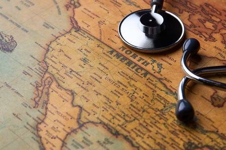 Medical stethoscope over North America healthcheck. Medical concept tourism travel care diseases healthy, close-up. Stethoscope on map background with copy space, top view, selective focus.