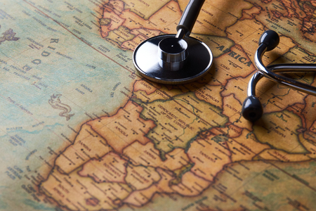 Medical stethoscope over Africa healthcheck. Fever vaccination concept tourism travel care diseases healthy, close-up. Stethoscope on map background with copy space, top view, selective focus.