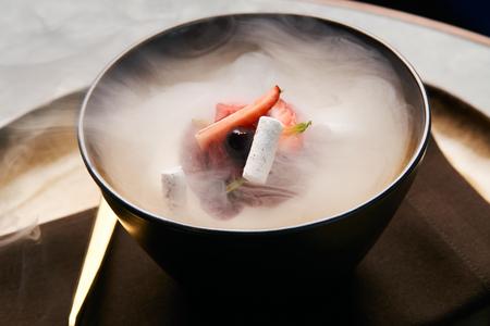 Cocinero chef haciendo helado de frutas con nitrógeno líquido. Postre frío con humo de hielo seco en placa, primer plano Foto de archivo