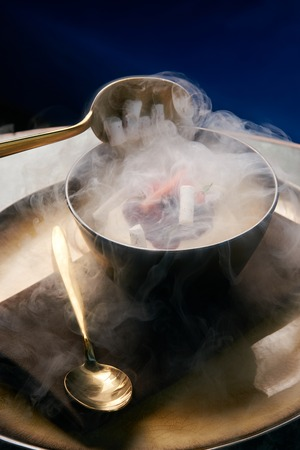 Cook chef making fruit ice cream added liquid nitrogen. Cold dessert food with dry ice smoke in plate, close-up Banque d'images