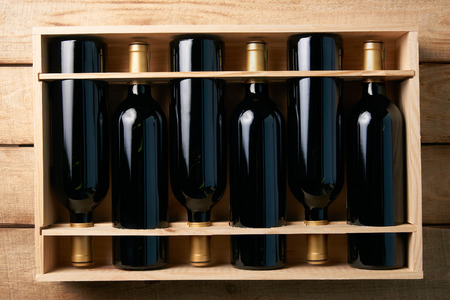 Wine bottles in wooden crate on wood table background, close-up. Red wine in wood box case in wine shop Banco de Imagens