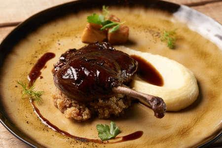 Gebratener Entenkeulenstock mit Quinoa-Püree, Sellerie, Apfel mit Zimtsauce auf Teller serviert. Exklusives Restaurantessen