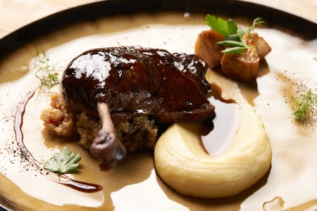 Roasted Duck drumstick with Quinoa puree, celery, apple with cinnamon sauce served on plate. Exclusive restaurant food