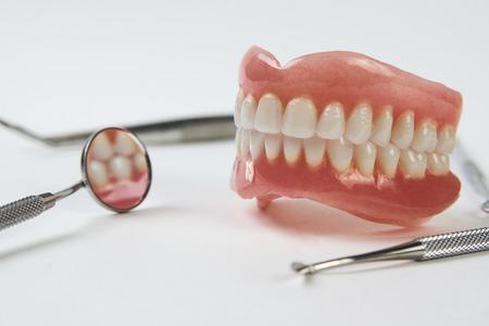 Künstliche Zähne auf weißem Hintergrund mit Kopienraum. Zahnarzttermin, zahnmedizinische Instrumente und Kontrollkonzept für Zahnhygieniker mit Zahnmodellprothesen und Mundspiegel