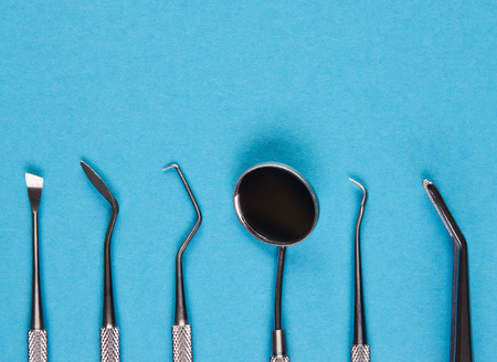 Professional Dentist tools in dental office close-up. Dentist mirror, forceps curved, explorer curved, dental explorer angular on a blue background with copy space top view. Medical healthcare concept Stock Photo