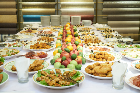 Catering table set service with cold snacks, canapes, fruits and vegetables. Reception Buffet table at party event. Luxury food and drinks on table.