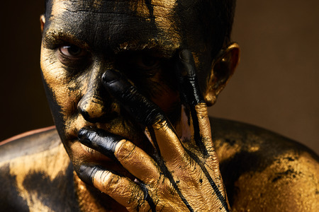 Golden Driller close-up portrait. Man covered with gold paint and black crude oil color. Make-up and halloween theme. Coal and Gold Miner, dirty worker against dark background. Hard Work Concept Stock fotó