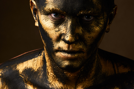 Hard Work Concept. Coal and Gold Miner, dirty worker against dark background. Man covered with gold paint and black crude oil color. Make-up and halloween theme. Stock fotó