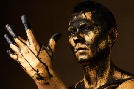 Make-up and halloween theme. Coal and Gold Miner, dirty worker against dark background. Hard Work Concept. Man covered with gold paint and black crude oil color.