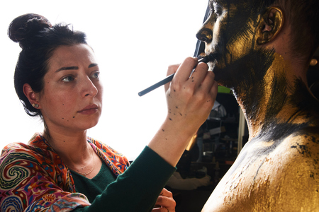 Professional makeup artist working with young man. Makeup artist working on models face in shooting break on movie set location, close-up Foto de archivo