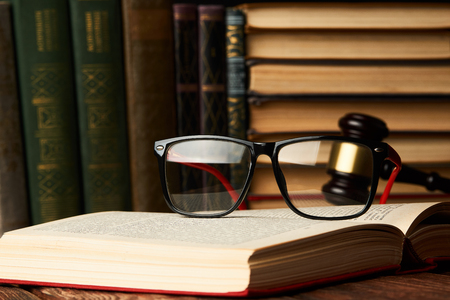 Judge gavel and legal book collection with eyeglasses on wooden table, Education justice and law concept, close-up Stock Photo