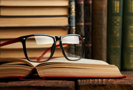 Old books and reading glasses on desk in library room. Education learning concept with opened book collection and eyeglasses, close-up