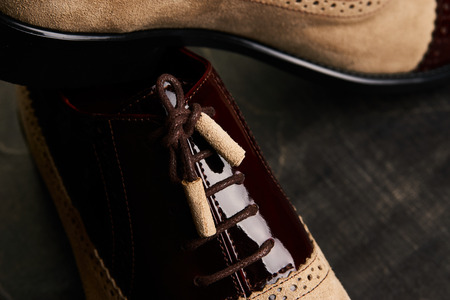 Grooms wedding shoes on a dark wooden box, close-up. Elegant mens shoes over brown background with copy space. Mens business fashion concept