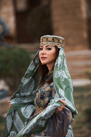 Azerbaijan national spring holiday Novruz celebration. Beautiful woman wearing oriental national clothes posing outdoor.