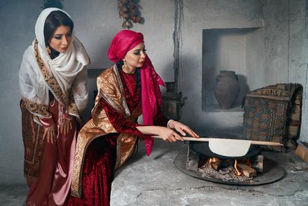 Woman preparing or making borek or bread dough. Girl friends keep rolling pin on dough with flour. Cooking traditional Turkish borek, pide, pita or yufka bread. Traditional Turkish food Banque d'images - 118196872