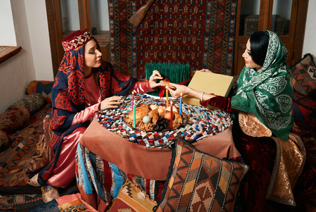 Novruz holiday celebration with Beautiful azeri women and novruz tray with traditional pastry shekerbura and pakhlava food.