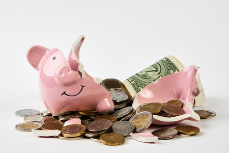 Broken piggy bank with coins money isolated on white background, close-up. Finance, saving money for travel