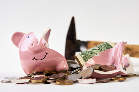 Broken piggy bank with coins money and hammer isolated on white background, close-up. Finance, saving money for travel