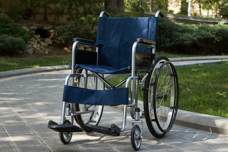 Empty wheelchair at the park, close-up. Empty modern disability wheelchair parked at hospital park, outdoors. Miracle concept. Healed person raised and went away, sadness and loneliness Stock fotó