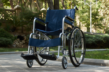 Empty wheelchair at the park, close-up. Empty modern disability wheelchair parked at hospital park, outdoors. Miracle concept. Healed person raised and went away, sadness and loneliness Imagens