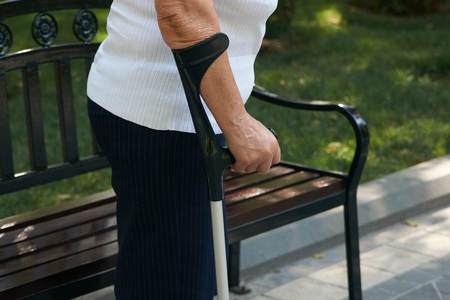 Senior woman using a walker, outdoors. Patient woman stand and holding walking stick, close-up. Elderly woman hand using walking stick in park. Medical and healthcare concept