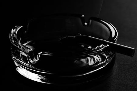 Cigarette and glass ashtray on black background with copy space, close-up. Black and white