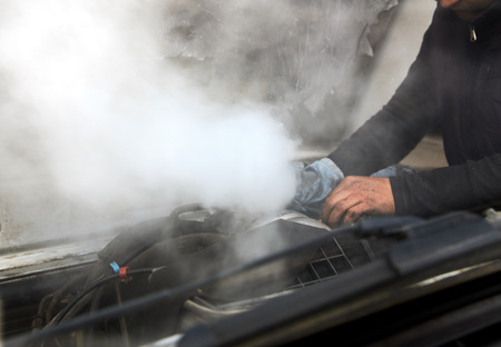 Man mechanic repair a smoking engine of his overheated car. Broken down old car with smoke or steam from hose. Stock Photo