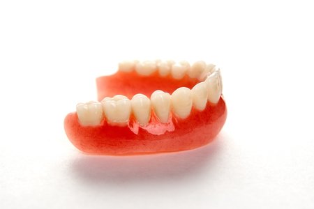 Artificial teeth on a white background with copy space. Dentist appointment, dentistry instruments and dental hygienist checkup concept with teeth model dentures Stock Photo