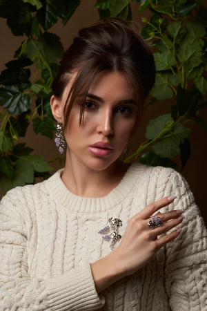 Beautiful young brunette woman in warm knitted white sweater.