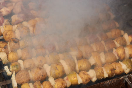 Preparation of shish kebab on skewers, close-up. Grilled shish kebab with vegetables. BBQ grill with lamb meat and potatoes