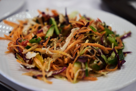 Mix vegetable salad on white dish, close-up. Healthy diet salad with fresh vegetables, red onion, cabbage, carrot, cucumber