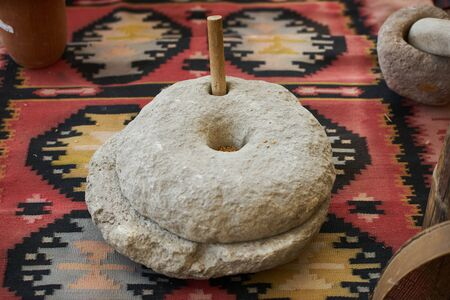 The ancient quern stone hand mill with grain. Retro wheat grain grinder, close-up. Farming and agriculture concept