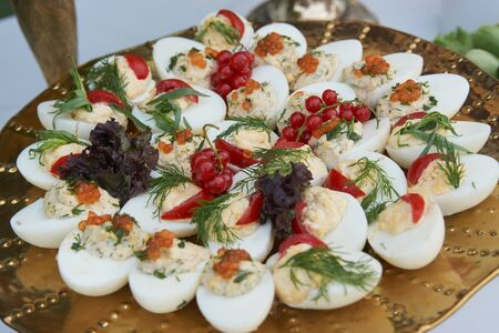Stuffed eggs canapes with soft cheese chive and caviar. Healthy food. Catering service buffet food at wedding event table, close-up.