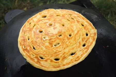Pita bread baking on a saj or tava on fire, close-up. Traditional arabic pita bread cooking on fire. Preparing or making borek