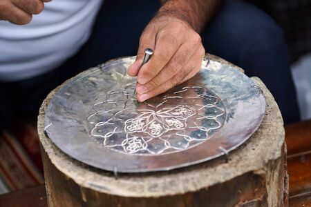 Handmade work with metal engraving. Craftsman working outdoors, close-up. 스톡 콘텐츠