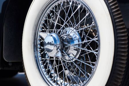 Closeup of vintage car wire wheel tyre. Retro car tire with silver wired disc