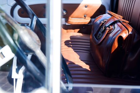Business travel concept with brown leather bag on old car seat. Vintage travel bag in retro car interior, vacation trip