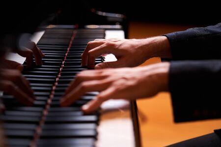 Hand des Nahaufnahmemannes, die Klavier spielt. Hand des Musikdarstellers, der die Flügeltastatur spielt
