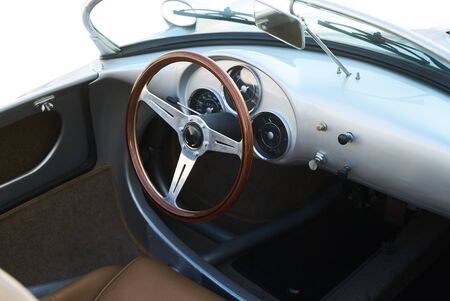 Vintage retro car interior, close-up. Drivers cockpit of a classic car. Old automobile steering wheel