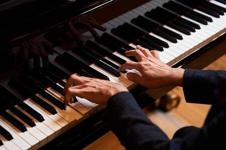Mano del hombre del primer que toca el piano. Mano del intérprete de música tocando el teclado del piano de cola Foto de archivo