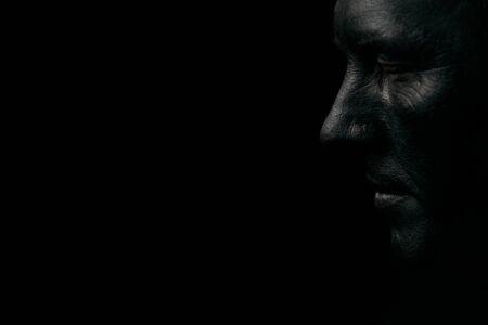 Make-up portret van een jonge man met zwart gezicht, close-up. Mijnwerker portret geïsoleerd op donkere achtergrond met kopie space