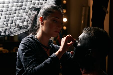 Professional makeup artist working on models face in shooting brake on movie set location, close-up Banco de Imagens