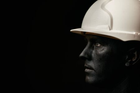 Hard Work Concept. Coal and Oil Miner, dirty worker against dark background. Man in white helmet covered with black paint and black crude oil color. Make-up and halloween theme