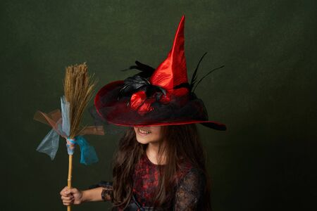 Cute child girl in witch costume for Halloween, close-up. Happy sisters on Halloween. Funny kids in carnival costumes on green background with copy space