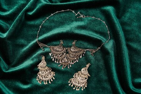 Silver necklace and earrings on a green silk background, close-up. Retro handmade jewelry Imagens