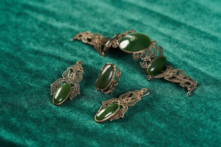 Beautiful jewellery set with earrings, ring and bracelet, close-up. Indian Bridal jewellery on green silk background Imagens