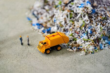 Garbage truck toy model and workers, close-up.
