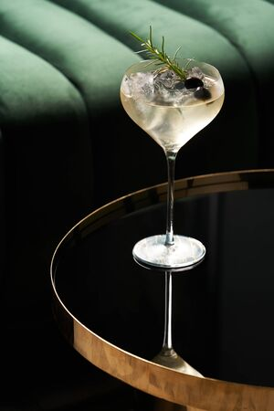 Classic cocktail glass on glass table in night club restaurant. Alcohol cocktail drink, close-up. Modern alcoholic beverage