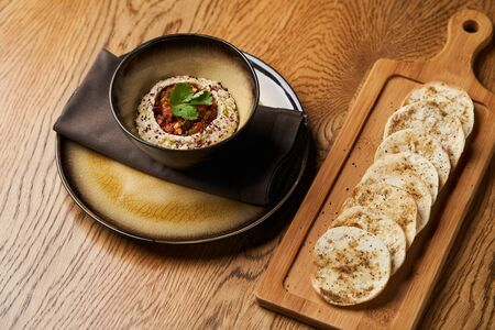 Baba ganoush hummus with eggplant on wooden table background. Traditional Middle Eastern cuisine, vegan aubergine hummus with pita bread toasts, close-up.